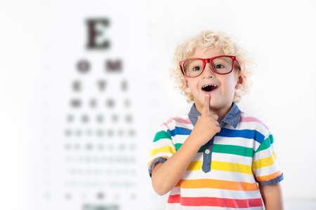 Kind bij gezichtsvermogen test. Weinig jong geitje die glazen selecteren bij opticienopslag. Gezichtsvermogenmeting voor schoolkinderen. Oogbescherming voor kinderen. Arts oogcontrole uitvoeren. Jongen met bril op de briefkaart. Stockfoto - 92113244