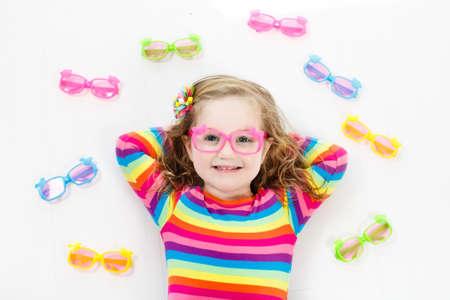 Kind bij gezichtsvermogen test. Weinig jong geitje die glazen selecteren bij opticienopslag. Gezichtsvermogenmeting voor schoolkinderen. Oogbescherming voor kinderen. Arts oogcontrole uitvoeren. Baby met bril bovenaanzicht.