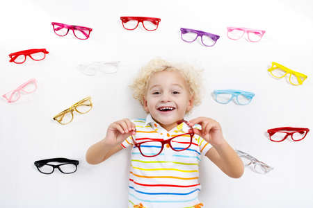 目の視力テストの子。小さな子供の眼鏡店でメガネを選択します。学校の子供たちの視力測定。子供の目の摩耗。目のチェックを実行する医師。眼