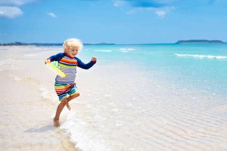 美しいビーチの子供。小さな男の子が走って、海岸でジャンプ。子供と海の休暇。子供たちは夏のビーチで遊びます。水の楽しみ。子供たちは走っ