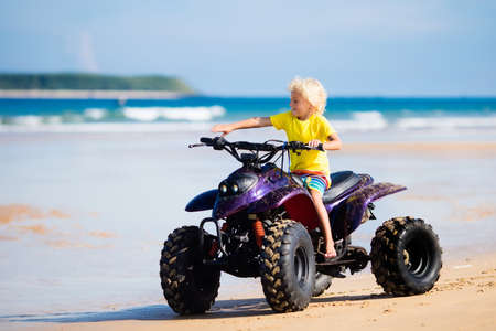 Little boy riding quad bike on tropical beach. Cute blond curly child on quadricycle. All-terrain vehicle ride. Motor cross sports on ocean sand dune. Kids summer vacation activity. Off road race. Stock Photo