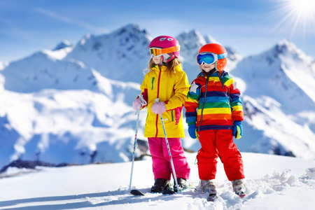 Child skiing in the mountains. Kid in ski school. Winter sport for kids. Family Christmas vacation in the Alps. Children learn downhill skiing. Alpine ski lesson for boy and girl. Outdoor snow fun. 스톡 콘텐츠