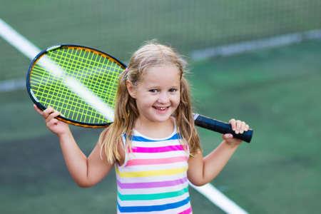 屋外コートでテニスをしている子供。スポーツクラブでテニスラケットとボールを持つ小さな女の子。子供のためのアクティブな運動。子供のため