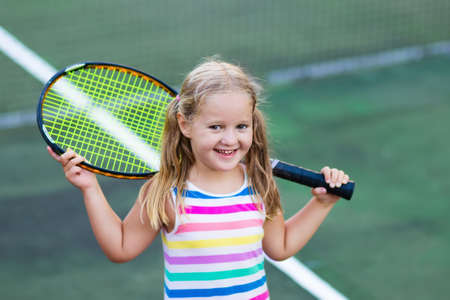 Child playing tennis on outdoor court. Little girl with tennis racket and ball in sport club. Active exercise for kids. Summer activities for children. Training for young kid. Child learning to play. Imagens - 94205198
