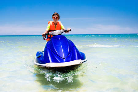 Teenager on jet ski. Teen age boy skiing on water scooter. Young man on personal watercraft in tropical sea. Active summer vacation for school child. Sport and ocean activity on beach holiday. Фото со стока - 94205218