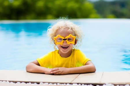 Child with goggles in swimming pool. Blond curly little boy learning to swim in outdoor pool of tropical resort. Swimming with kids. Healthy sport activity for children. Sun protection. Water fun.