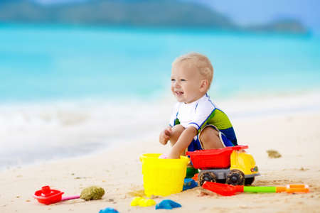 Child playing on tropical beach. Little girl digging sand at sea shore. Family summer vacation. Kids play with water and sand toys. Ocean and island fun. Travel with young children. Asia holiday.