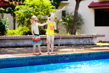 Kids playing with garden hose in backyard with large outdoor swimming pool. Children play with water. Swim wear and toys for boy and girl. Family summer vacation with hot sunny weather. Garden pool. Stok Fotoğraf