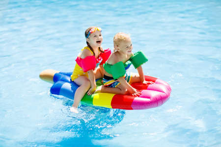 Boy and girl on inflatable ice cream float in outdoor swimming pool of tropical resort. Summer vacation with kids. Swim aids and wear for children. Water toys. Little child floating on colorful raft.