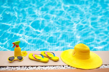 Zwembadaccessoires liggen plat. Hoogste mening van strandpunten op pooldek. Slippers, bikini en hoed, zonnebril. Waterspeelgoed. Zomervakantie in tropisch resort. Ruimte kopiëren. Kleurrijke strandslijtage. Stockfoto