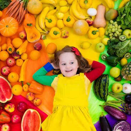 Bambina con varietà di frutta e verdura. Arcobaleno variopinto di frutta e verdure fresche crude. Bambino che mangia spuntino sano. Alimentazione vegetariana per bambini Vitamine per bambini. Vista dall'alto Archivio Fotografico - 94212492