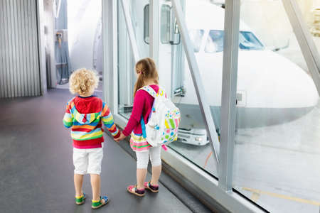 Kids at airport. Children look at airplane. Traveling and flying with child. Family at departure gate. Vacation and travel with young kid. Boy and girl before flight in terminal. Kids fly a plane. Stok Fotoğraf