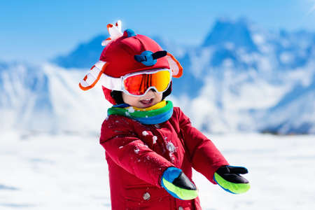 Child skiing in the mountains. Kid in ski school. Winter sport for kids. Family Christmas vacation in the Alps. Children learn downhill skiing. Alpine ski lesson for boy or girl. Outdoor snow fun. Imagens