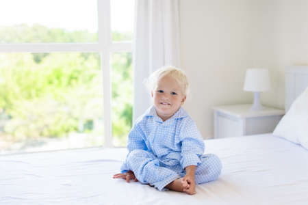 Kids playing in parents bed. Children wake up in sunny white bedroom. Little boy in blue pajamas. Sleepwear and bedding for child and baby. Nursery interior for toddler kid. Family morning. Stock Photo