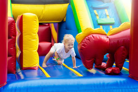 Child jumping on colorful playground trampoline. Kids jump in inflatable bounce castle on kindergarten birthday party Activity and play center for young child. Little boy playing outdoors in summer.