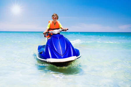 Teenager on jet ski. Teen age boy skiing on water scooter. Young man on personal watercraft in tropical sea. Active summer vacation for school child. Sport and ocean activity on beach holiday. Фото со стока