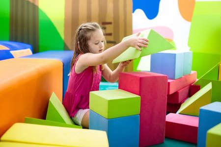 Kind, das mit bunten Aufbaubauklötzen spielt. Lernspielzeug für kleine Kinder. Kindergarten oder Vorschulspielzimmer. Kleinkindkind am Kindertagesstättenspielplatz. Mädchengebäudehaus mit Block am Kindertagesstätte Standard-Bild