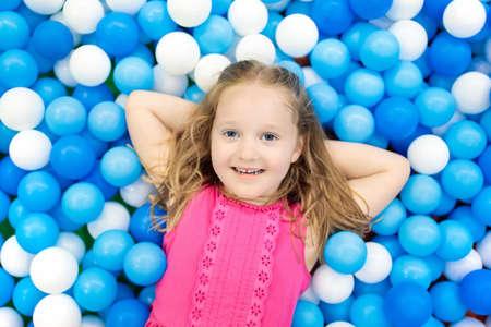 Kind spelen in ballenbak. Kleurrijk speelgoed voor kinderen. Kleuterschool of voorschoolse speelkamer. Peuterjong geitje bij kinderdagverblijf binnenspeelplaats. Ballenbad voor kinderen. Verjaardagsfeest voor actieve kleuter.