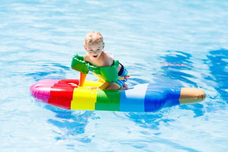 Happy child on inflatable ice cream float in outdoor swimming pool of tropical resort. Summer vacation with kids. Swim aids and wear for children. Water toys. Little girl floating on colorful raft. Reklamní fotografie - 94212615
