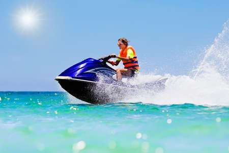 Teenager on jet ski. Teen age boy skiing on water scooter. Young man on personal watercraft in tropical sea. Active summer vacation for school child. Sport and ocean activity on beach holiday. Banque d'images