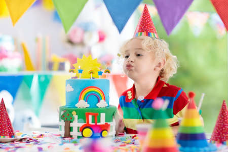 Kids birthday party. Child blowing out candles on colorful cake. Decorated home with rainbow flag banners, balloons. Farm and transport theme celebration. Little boy celebrating birthday. Party food.