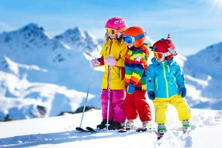 Esqui aquático nas montanhas. Criança na escola de esqui. Desportos de inverno para crianças. Férias de Natal familiar nos Alpes. As crianças aprendem esqui alpino. Lição de esqui alpina para menino e menina. Diversão ao ar livre na neve. Foto de archivo
