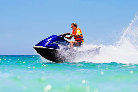 Teenager on jet ski. Teen age boy skiing on water scooter. Young man on personal watercraft in tropical sea. Active summer vacation for school child. Sport and ocean activity on beach holiday. Stock Photo