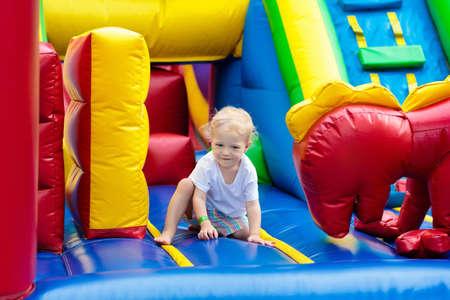 Das Kind springend auf bunte Spielplatztrampoline. Kinder springen in aufblasbare Hüpfburg auf Kindergartengeburtstagsfeier Aktivitäts- und Spielzentrum für Kleinkinder. Kleiner Junge, der draußen im Sommer spielt. Standard-Bild - 94358048