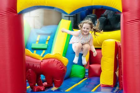 El niño que salta en el trampolín colorido del patio. Los niños saltan en el castillo de rebote inflable en la fiesta de cumpleaños del jardín de infantes. Centro de actividades y juegos para niños pequeños. Niña jugando al aire libre en verano.