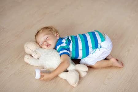 Babyslaap op een houten vloer met een gevuld stuk speelgoed. Grappig moe jongetje in slaap vallen kruipen op hardhouten vloer thuis. Slaperige zuigelingenvoeding op zacht kussen.