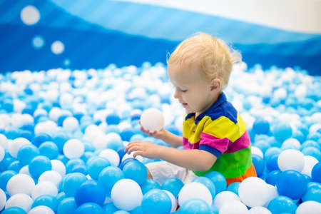Child playing in ball pit. Colorful toys for kids. Kindergarten or preschool play room. Toddler kid at day care indoor playground. Balls pool for children. Birthday party for active preschooler.