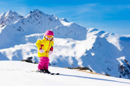 Child skiing in mountains. Active toddler kid with safety helmet, goggles and poles. Ski race for young children. Winter sport for family. Kids ski lesson in alpine school. Little skier racing in snow 写真素材