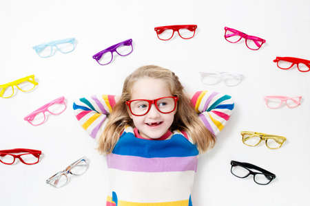 Child at eye sight test. Little kid selecting glasses at optician store. Eyesight measurement for school kids. Eye wear for children. Doctor performing eye check. Girl with spectacles at letter chart. 写真素材