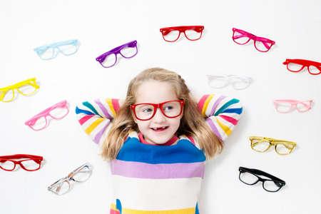 Kind bij gezichtsvermogen test. Weinig jong geitje die glazen selecteren bij opticienopslag. Gezichtsvermogenmeting voor schoolkinderen. Oogbescherming voor kinderen. Arts oogcontrole uitvoeren. Meisje met bril op de briefkaart. Stockfoto