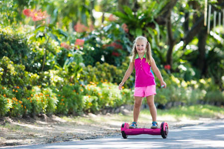 Child on hover board. Kids riding scooter in summer park. Balance board for children. Electric self balancing scooter on city street. Girl learning to ride hoverboard. Modern gadgets for school kid. Stock Photo - 94987726