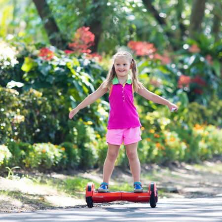 Child on hover board. Kids riding scooter in summer park. Balance board for children. Electric self balancing scooter on city street. Girl learning to ride hoverboard. Modern gadgets for school kid. Stock Photo - 94987806