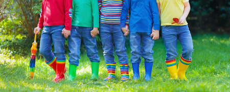 Kids in rain boots. Group of kindergarten children in colorful rubber boots and autumn jackets. Footwear for rainy fall. Foot wear for child and baby. Toddler in wellies. Rainbow gumboots. Kid fashion