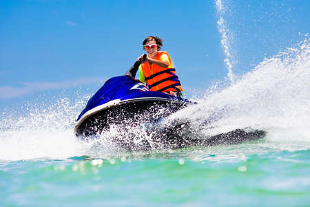 Teenager on jet ski. Teen age boy skiing on water scooter. Young man on personal watercraft in tropical sea. Active summer vacation for school child. Sport and ocean activity on beach holiday. 스톡 콘텐츠