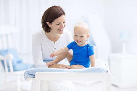 엄마와 아기 기저귀 변경 테이블에. 아기 소년에 기저귀를 바꾸는 엄마. 키즈 보육원. 유아 위생 용품. 어린 이용 기저귀. 흰색 침실에 아이 함께 노는  스톡 콘텐츠