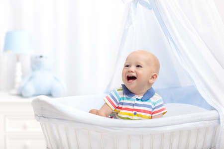 Baby drinking milk in white crib. Infant boy with formula bottle in bed. Kids nutrition. Healthy food and drink for children. Child in white nursery. Baby room interior. Kid with toy and milk bottle.