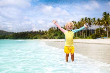 美しいビーチの子供。おもちゃのボートを持つ小さな男の子が走って、海岸でジャンプ。子供と海の休暇。子供たちは夏のビーチで遊びます。水の