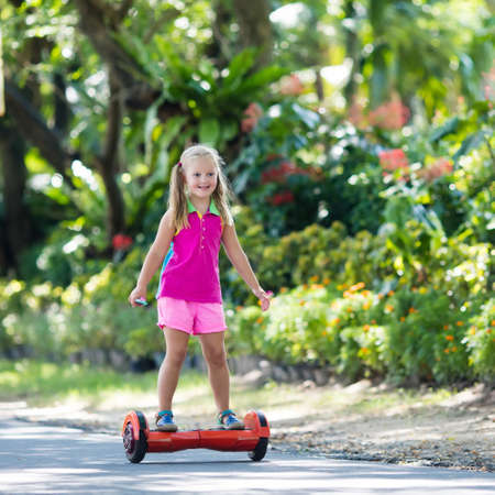 Child on hover board. Kids riding scooter in summer park. Balance board for children. Electric self balancing scooter on city street. Girl learning to ride hoverboard. Modern gadgets for school kid.