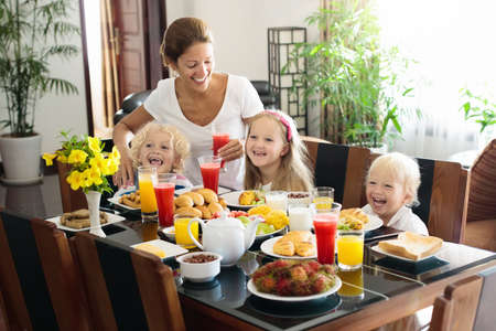 Healthy family breakfast at home. Mother and kids eating tropical fruit, toast bread, cheese and sausage. Children drink fresh pressed juice on sunny morning. Mom, boy, girl and baby eat breakfast. Reklamní fotografie