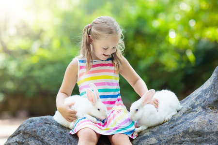 Child playing with rabbit. Little girl feeding white bunny. Easter celebration. Egg hunt with kid and pet animal. Children and animals. Kids take care of pets. Spring Easter garden with two rabbits.