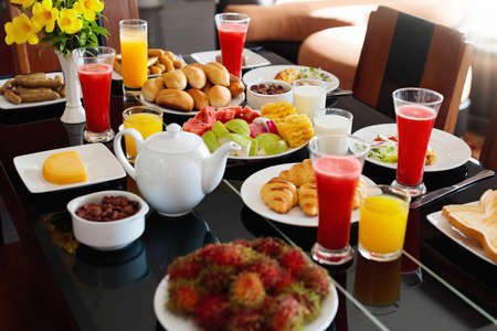 Healthy breakfast with bread and sausage on dark wooden table. Tropical fruit, fresh pressed juice, toast and croissants served for family breakfast on sunny morning. Variety of lunch and branch food. Stock Photo