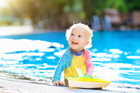Baby with toy boat in swimming pool. Little boy learning to swim in outdoor pool of tropical resort. Swimming with kids. Healthy sport activity for children. Sun protection swim wear. Water toys.
