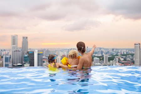 Family swimming in roof top outdoor pool on family vacation in Singapore. City skyline from infinity pool in luxury hotel. Kids swim and enjoy skyscraper view in Asia. Travel with young children.