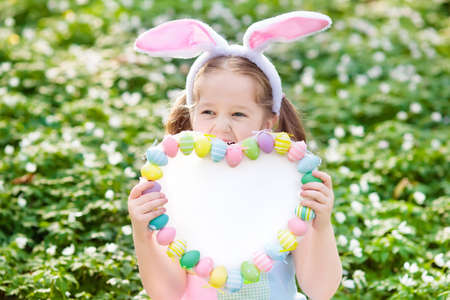 Easter egg hunt in spring garden. Kids searching for colorful eggs and sweets hidden in blooming flower field. Child with bunny ears and egg basket. Family Easter celebration. White board for text. Stock Photo