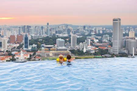 Bambini che nuotano nello stagno all'aperto della cima del tetto sulla vacanza di famiglia a Singapore. Skyline della città dalla piscina a sfioro in hotel di lusso. I bambini nuotano e godono della vista del grattacielo in Asia. Viaggia con un bambino piccolo. Archivio Fotografico - 96433949
