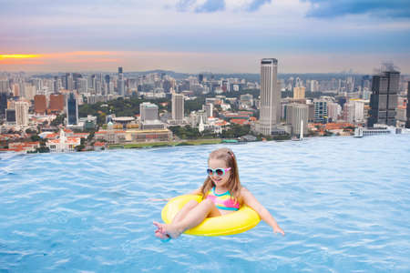 Children swimming in a roof top outdoor pool on a family vacation in Singapore. City skyline from infinity. Kids swim and enjoy skyscraper view in Asia. Travel with young child.